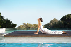 Peaceful brunette in cobra pose poolside Royalty Free Stock Images
