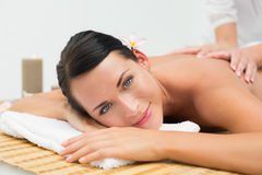 Peaceful brunette enjoying a back massage smiling at camera Royalty Free Stock Images
