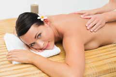 Peaceful brunette enjoying a back massage smiling at camera Royalty Free Stock Photos