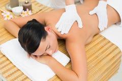 Peaceful brunette enjoying an exfoliating back massage Royalty Free Stock Photo