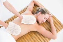 Peaceful brunette enjoying an exfoliating back massage Royalty Free Stock Photography