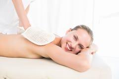Peaceful brunette enjoying an exfoliating back massage Stock Photos