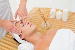 Peaceful brunette enjoying a face massage Stock Photo