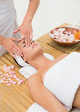 Peaceful brunette enjoying a face massage Stock Photos
