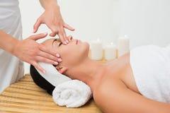 Peaceful brunette enjoying a face massage Stock Image