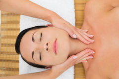 Peaceful brunette enjoying a facial massage Royalty Free Stock Photo