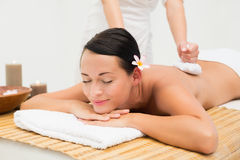 Peaceful brunette enjoying a herbal compress massage Stock Images