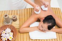 Peaceful brunette enjoying a herbal compress massage Royalty Free Stock Image