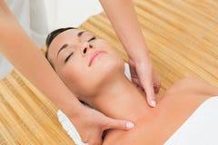 Peaceful brunette enjoying a neck massage Royalty Free Stock Photo