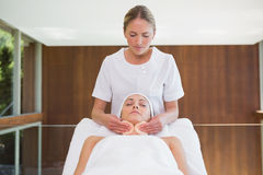 Peaceful brunette getting facial from beauty therapist Royalty Free Stock Photo