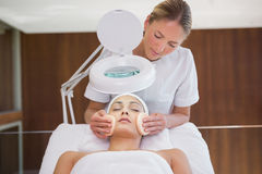 Peaceful brunette getting facial from beauty therapist Stock Photos