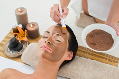 Peaceful brunette getting a mud facial applied Royalty Free Stock Photo