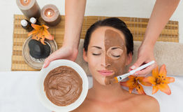Peaceful brunette getting a mud facial applied Royalty Free Stock Images