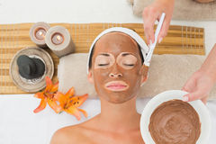 Peaceful brunette getting a mud treatment facial Royalty Free Stock Photos