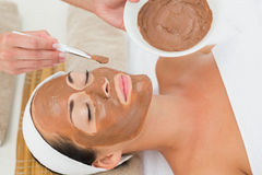 Peaceful brunette getting a mud treatment facial Stock Image