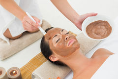 Peaceful brunette getting a mud treatment facial Stock Photo