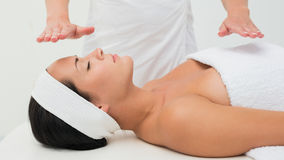 Peaceful brunette getting reiki therapy Stock Photography