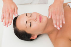 Peaceful brunette getting reiki therapy Royalty Free Stock Image