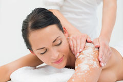 Peaceful brunette getting a salt scrub beauty treatment. In the health spa Royalty Free Stock Images