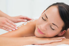 Peaceful brunette getting a salt scrub beauty treatment Royalty Free Stock Photography