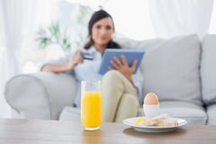 Peaceful brunette having breakfast while buying online Stock Photos