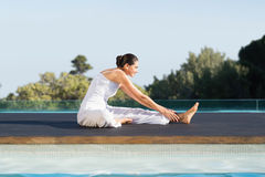 Peaceful brunette in janu sirsasana yoga pose poolside Stock Image