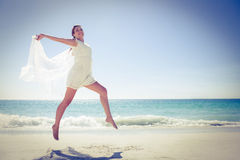 Peaceful brunette jumping at the beach. On a sunny day Stock Photo