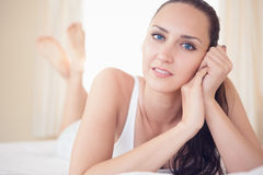 Peaceful brunette lying on bed and smiling at camera Stock Images