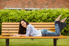 Peaceful brunette lying on bench using laptop Stock Photos