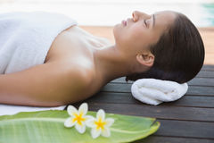 Peaceful brunette lying with eyes closed on a towel Stock Images