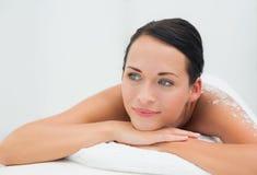 Peaceful brunette lying with salt scrub on back Royalty Free Stock Image