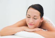 Peaceful brunette lying with salt scrub on back Royalty Free Stock Photo