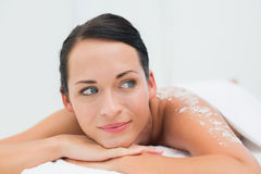 Peaceful brunette lying with salt scrub on back Royalty Free Stock Photography