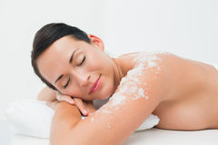 Peaceful brunette lying with salt scrub on shoulders Stock Photo