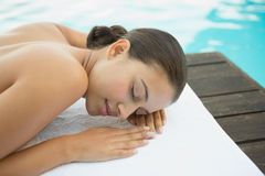 Peaceful brunette lying on towel poolside Stock Image