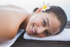 Peaceful brunette lying on towel smiling at camera Stock Images
