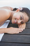 Peaceful brunette lying on towel smiling at camera Royalty Free Stock Image