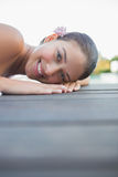 Peaceful brunette lying on towel smiling at camera Royalty Free Stock Images