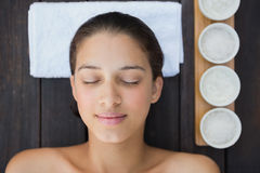 Peaceful brunette lying on towel with treatments beside her Royalty Free Stock Images