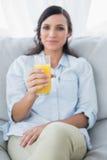 Peaceful brunette offering orange juice to camera Royalty Free Stock Image