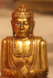 Peaceful Buddha Statue. Peaceful Golden Buddha Statue Opening Bright Blue Eye Stock Photo