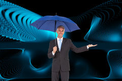 Peaceful businessman holding blue umbrella Stock Photo