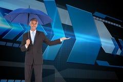 Peaceful businessman holding blue umbrella Stock Photos