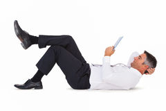 Peaceful businessman lying and using tablet pc Stock Photo