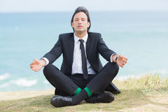 Peaceful businessman sitting in lotus pose relaxing Royalty Free Stock Image