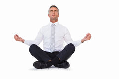 Peaceful businessman sitting in lotus pose Stock Photos