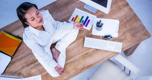 Peaceful businesswoman doing yoga sitting on floor Stock Photo