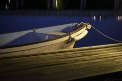 A small wooden boat parked at the dock or pier at night. Night photography with blue smooth waters. royalty free stock image