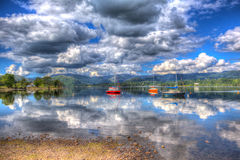 Peaceful calm lake with red orange and blue sailing boats in HDR Ullswater The English Lakes. Peaceful calm lake with red orange and blue sailing boats with stock photo