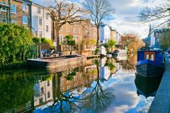 Peaceful canal scene. Regent`s canal, London, March 2010: Idyllic canal scene with boats, buildings, trees and reflection royalty free stock photography